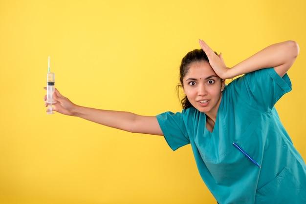 Vista frontale del giovane medico femminile con la siringa che tiene la testa sulla parete gialla