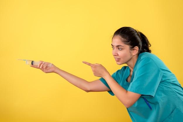 Vista frontale del giovane medico femminile con la siringa sulla parete gialla