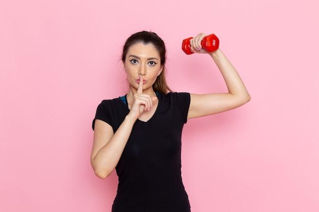 Giovane donna di vista frontale che fa sport e che tiene i manubri sugli allenamenti di salute di esercizio di sport dell'atleta della parete rosa