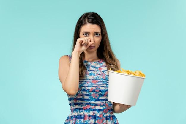 Вид спереди молодая женщина ест чипсы и смотрит фильм, плачет на синей поверхности
