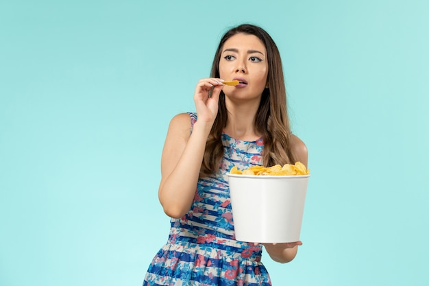 Вид спереди молодая женщина ест чипсы и смотрит фильм на синей поверхности