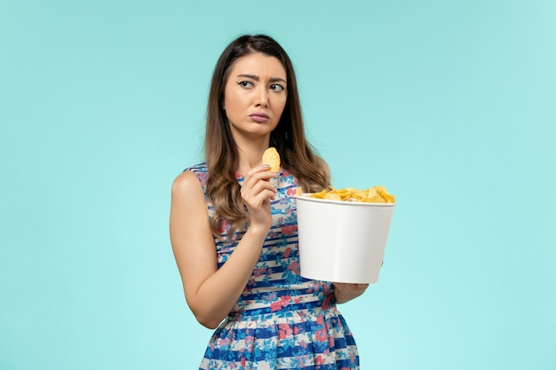 Вид спереди молодая женщина ест чипсы на светло-голубой поверхности