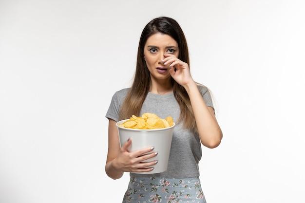 Giovane femmina di vista frontale che mangia cips e che guarda film sulla superficie bianca chiara