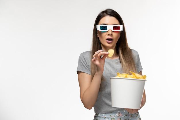 Giovane femmina di vista frontale che mangia cips mentre guarda film in occhiali da sole d su superficie bianca chiara