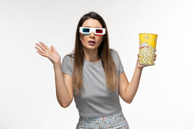 ポップコーンを食べて、明るい白い表面にサングラスで映画を見ている若い女性の正面図