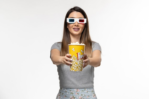 Вид спереди молодая женщина ест попкорн и смотрит фильм в солнцезащитных очках на светлой белой поверхности