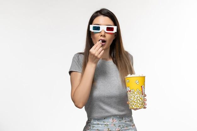 Вид спереди молодая женщина ест попкорн и смотрит фильм в солнцезащитных очках на белой поверхности