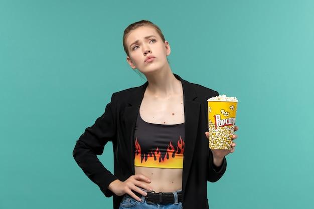 Вид спереди молодая женщина ест попкорн и смотрит фильм на синей поверхности