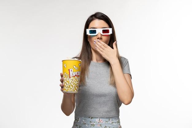 Вид спереди молодая женщина ест пакет попкорна и смотрит фильм в солнцезащитных очках на белом столе