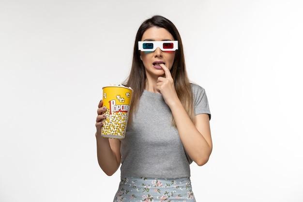 Giovane femmina di vista frontale che mangia pacchetto del popcorn e che guarda film in occhiali da sole d su superficie bianca