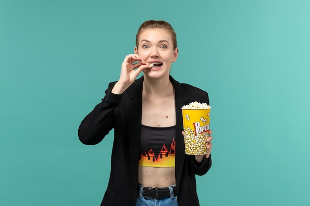 Front view young female eating popcorn and watching movie on blue surface