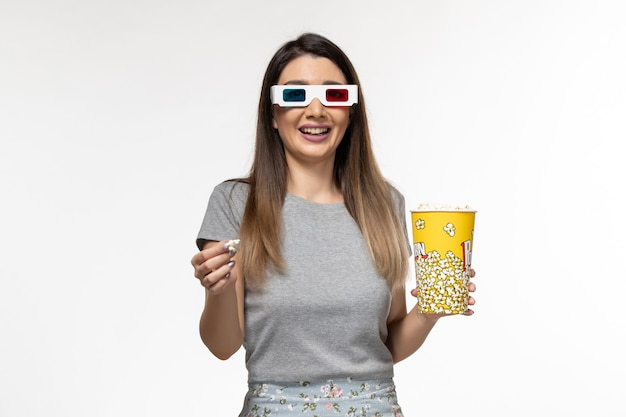 Giovane femmina di vista frontale che mangia popcorn e che guarda film in occhiali da sole d su superficie bianca