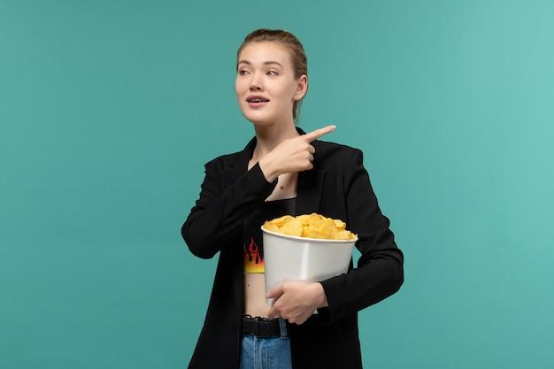 Вид спереди молодая женщина ест картофельные чипсы, смотрит фильм на синем столе
