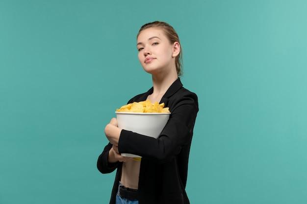 青い表面で映画を見ているポテトチップスを食べる若い女性の正面図