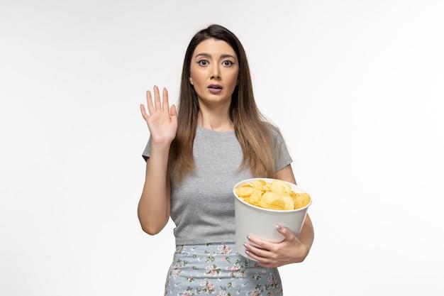 白い表面で映画を見ているポテトチップスを食べる若い女性の正面図