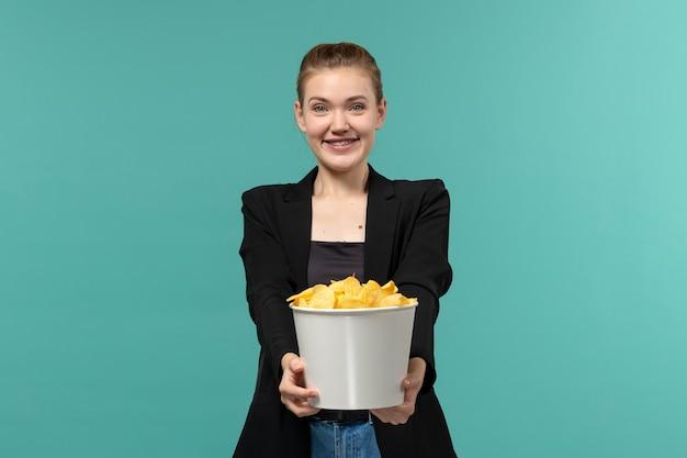 Вид спереди молодая женщина ест картофельные чипсы, смотрит фильм и улыбается на синей поверхности