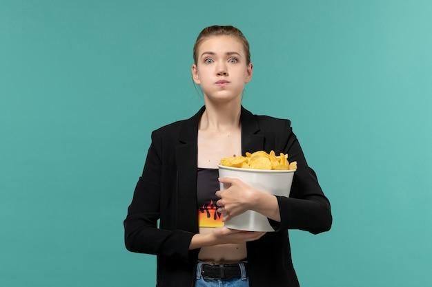 Giovane femmina di vista frontale che mangia patatine fritte che guarda film sullo scrittorio blu