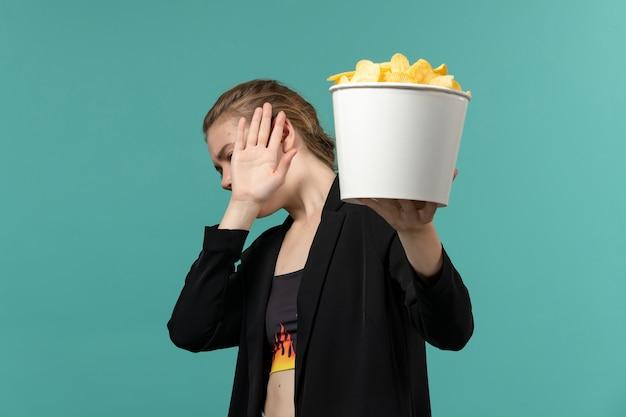 青い机の上で映画を見ているポテトチップスを食べる若い女性の正面図