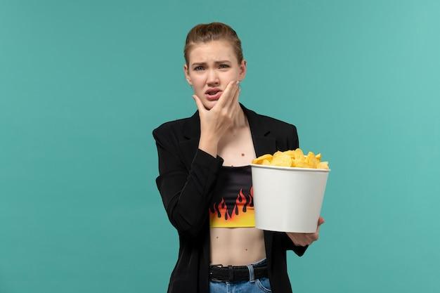 Вид спереди молодая женщина ест картофельные чипсы, смотрит фильм на синей поверхности