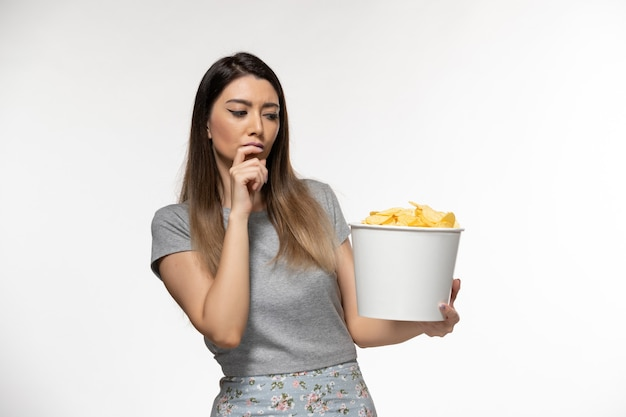 밝은 흰색 표면에 영화를보고 감자 칩을 먹는 전면보기 젊은 여성