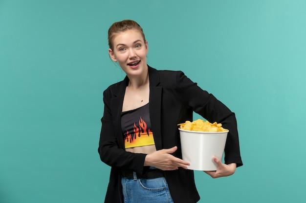 Вид спереди молодая женщина ест картофельные чипсы, смотрит фильм на голубой поверхности