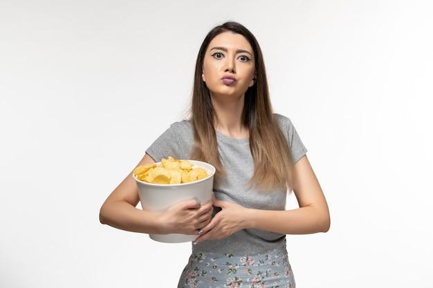 明るい白い表面で映画を見ているポテトチップスを食べる若い女性の正面図