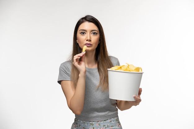 흰색 표면에 영화를보고 감자 칩을 먹는 전면보기 젊은 여성