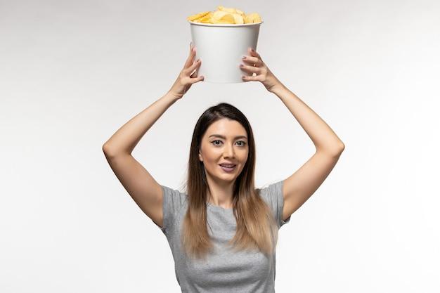 白い机の上で映画を見ているポテトチップスを食べる若い女性の正面図