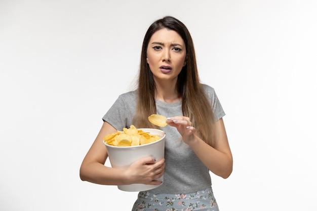 白い表面で映画を見ながらポテトチップスを食べる若い女性の正面図