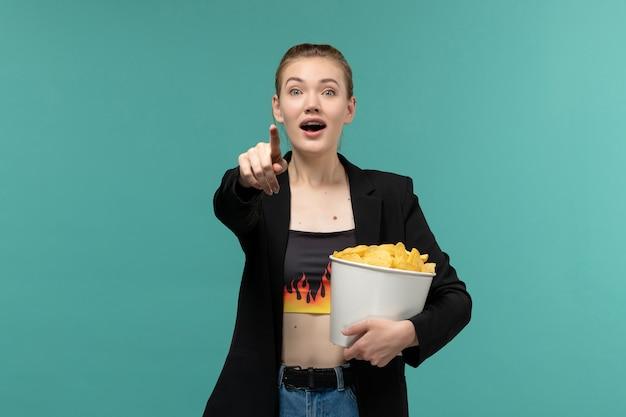 Giovane femmina di vista frontale che mangia le patatine fritte e che guarda film sulla superficie blu