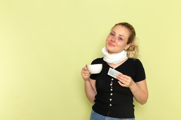 正面図緑の壁にコーヒーと薬を持って非常に病気と病気を感じている若い女性病気薬病気の健康