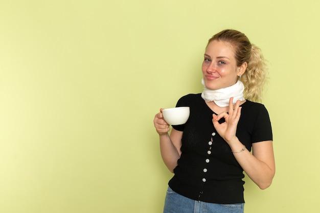 正面図若い女性は非常に病気と病気を感じて一杯のコーヒーを持って、緑の机の上で笑っている病気の薬病気の健康