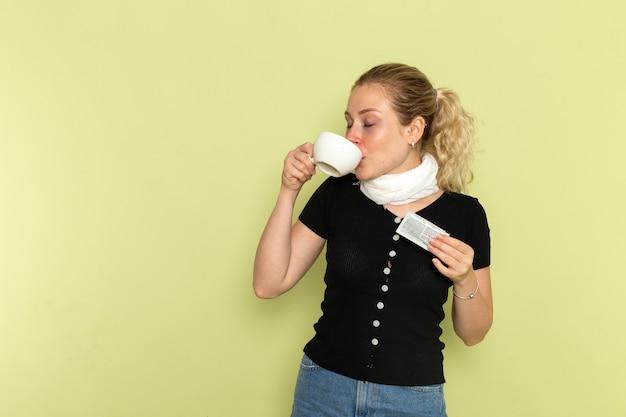 녹색 벽 질병 의학 질병 건강에 마시는 커피 한잔을 들고 매우 아프고 아픈 느낌 전면보기 젊은 여성