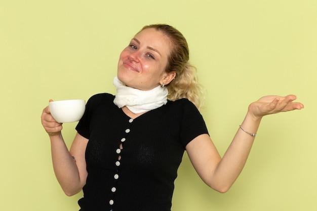 正面図若い女性は非常に気分が悪く、薄緑色の壁の病気の薬の病気でコーヒーを持って病気になっています