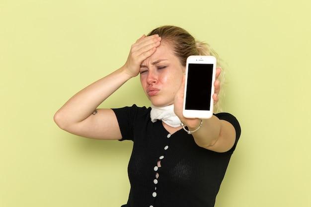 Вид спереди молодая женщина чувствует себя очень больной и больной, держа свой телефон на зеленом столе