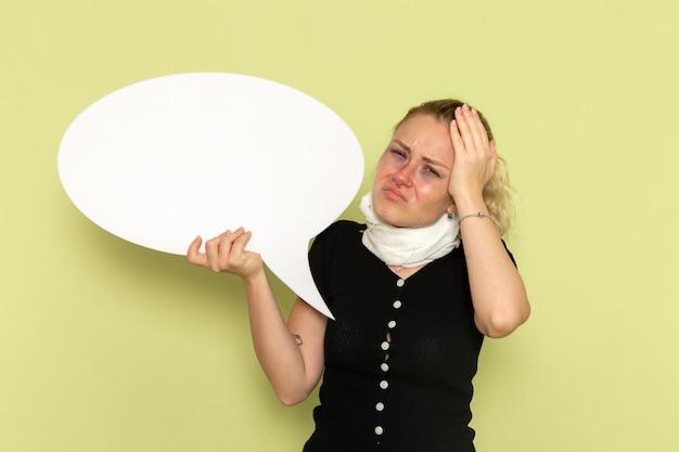正面図緑の壁の病気の薬の健康の病気に巨大な白い看板と彼女の頭を保持している非常に病気と病気を感じている若い女性