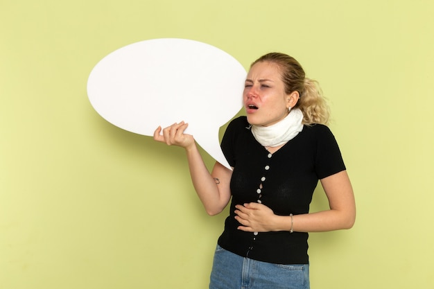 Вид спереди молодая женщина чувствует себя очень больной и больной, держит огромный белый знак и ее живот на зеленой стене болезнь медицина болезнь здоровье