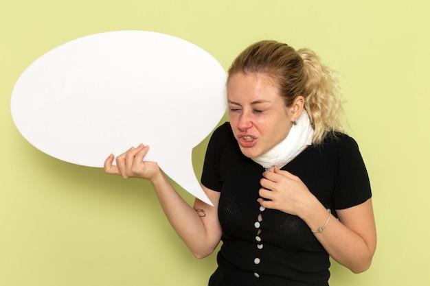 正面図若い女性は非常に病気と病気を感じて巨大な白い看板を保持し、緑の壁の病気の薬の健康病にくしゃみをします