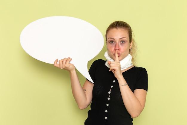 緑の壁の病気の薬の健康の病気で静かにすることを求める巨大な白い看板を持って非常に病気と病気を感じている正面図若い女性