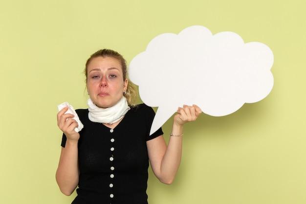 正面図若い女性は非常に病気と病気を感じて巨大な白い看板を持って薄緑色の壁に彼女の鼻をきれいにする