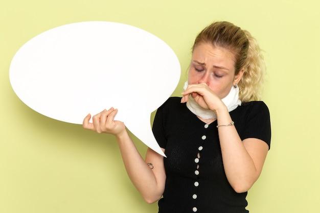 緑の壁の病気の薬の健康の病気で彼女の鼻を掃除する巨大な白い看板を持って非常に病気と病気を感じている正面図若い女性