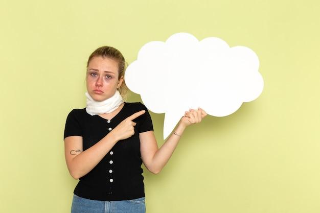 正面図緑の壁に巨大な白い看板を持って非常に病気と気分が悪い若い女性病気薬健康病