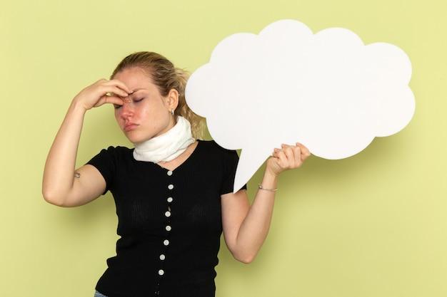 正面図若い女性は非常に病気と気分が悪い、薄緑色の壁に巨大な白い看板を持っている病気の薬健康病気の女の子