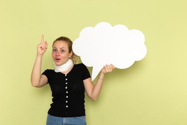正面図若い女性は非常に病気と気分が悪い、薄緑色の壁に巨大な白い看板を持っている病気医学健康病