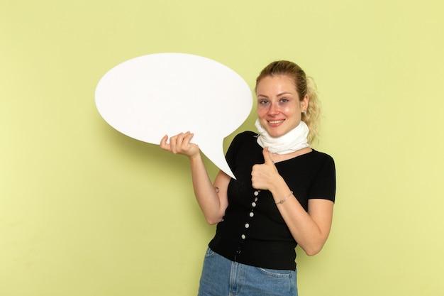 正面図緑の壁の病気の薬の病気の健康にポーズをとって笑っている巨大な白い看板を持って非常に病気と病気を感じている若い女性