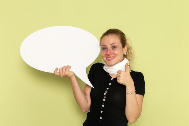 緑の壁の病気の薬の病気の健康にポーズをとって巨大な白い看板を保持している非常に病気と病気を感じている正面図若い女性