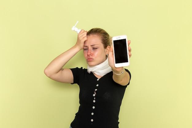正面図若い女性は非常に病気と病気を感じて電話を保持し、緑の壁の病気の薬の病気にスプレーします