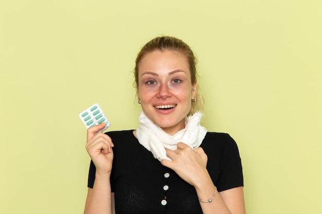 전면보기 젊은 여성은 매우 아프고 아픈 약을 들고 녹색 벽병 여성 의학 질병에 웃고