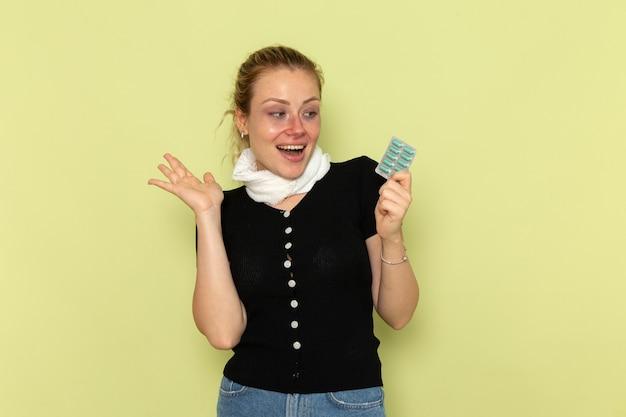 밝은 녹색 벽 질병 여성 의학 질병에 매우 아프고 아픈 약을 들고 전면보기 젊은 여성 느낌