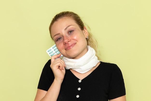 녹색 책상 질병 여성 의학 질병에 매우 아프고 아픈 약을 들고 전면보기 젊은 여성 느낌